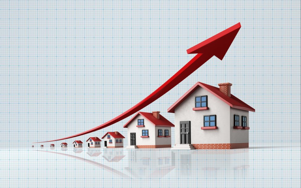 High quality 3d render of miniature houses on a blue graph paper. Housing market concept. Miniature houses are lit by the upper left corner of composition. A red arrow in the composition is symbolizing a sharp increase in sales. Vertical composition with copy space. Great use for real estate and mortgage related concepts.