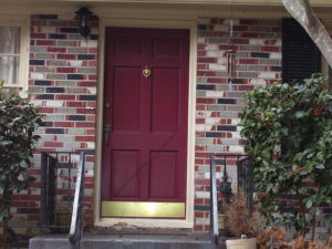 Red front door in a brick house