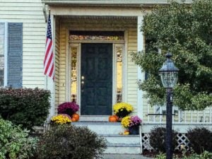 blue front door in yellow house with U.S.A. flag