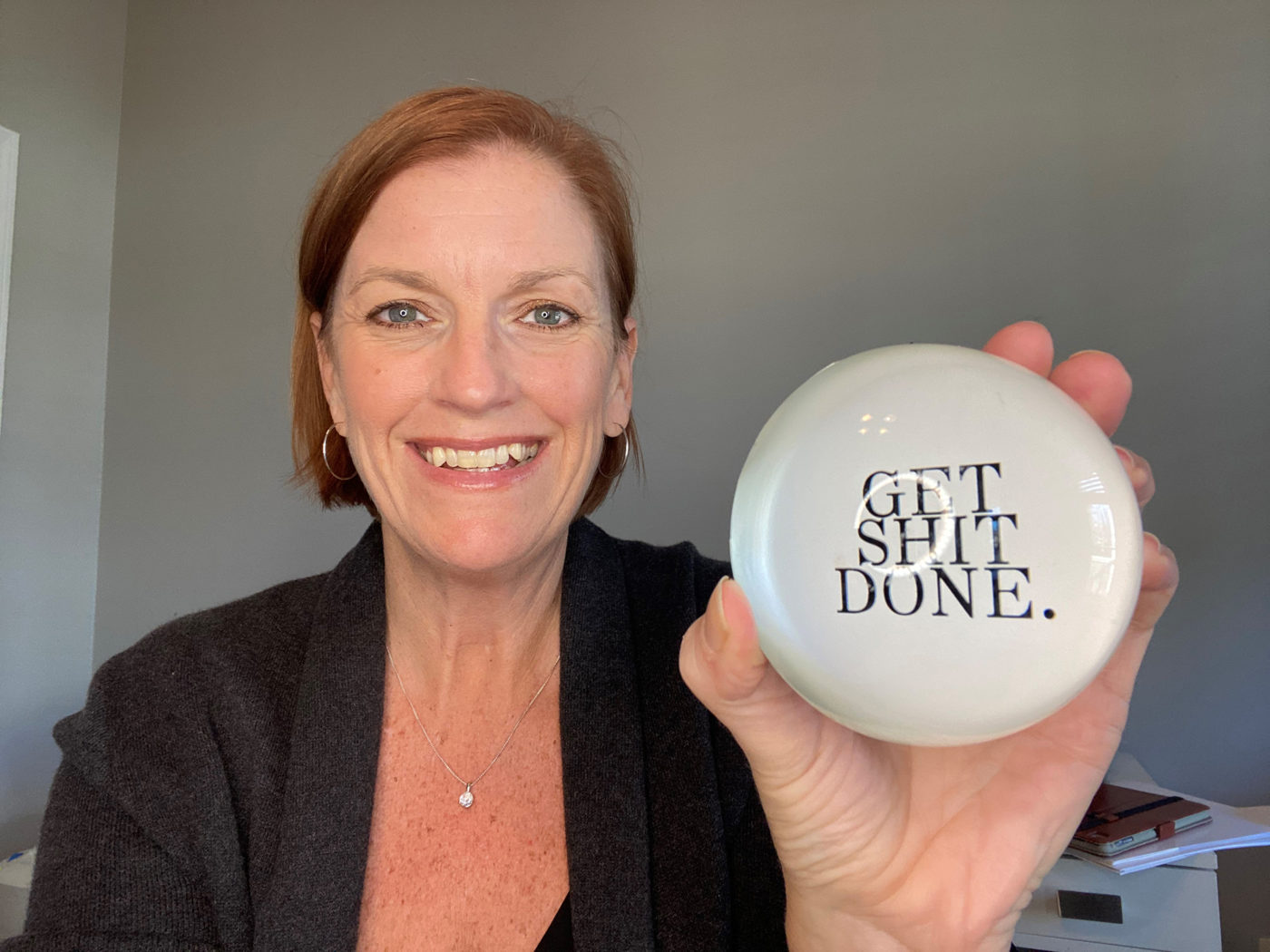 Melanie Cameron holding a paperweight that says Get Shit Done