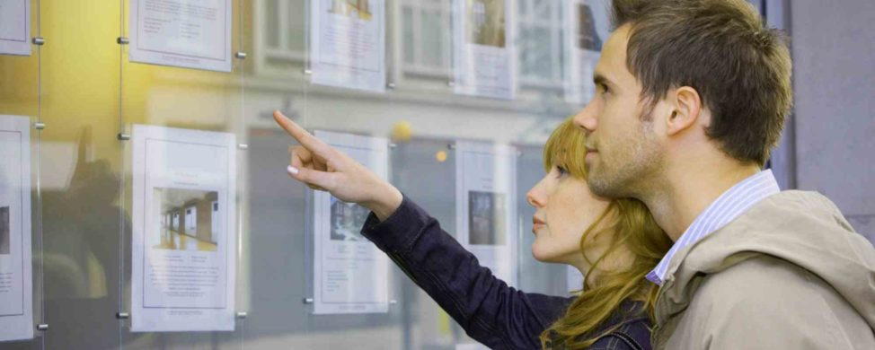 A couple looks at flyers for homes for sale in window