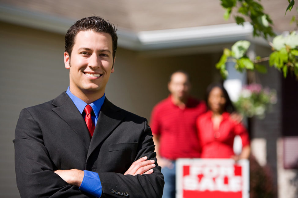 Real estate agent standing outside home with buyers