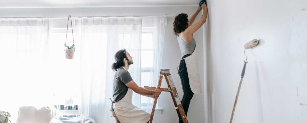 A man and woman work on painting a room.