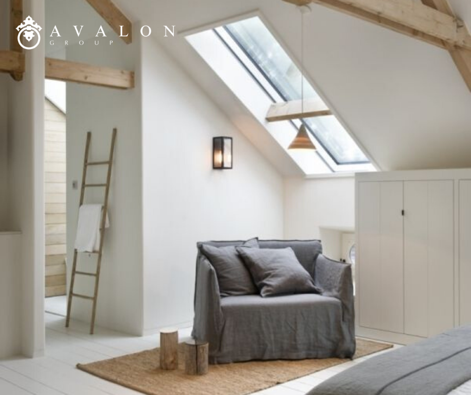 Furthermore, the pictures shows an attic remodel with a skylight in the slanted ceiling. Also, under the skylight is a large chair that is covered in a linen gray fabric.