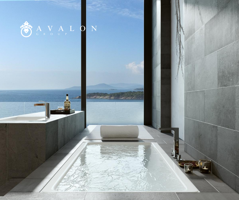 Moreover, the white elongated spa tub is filled with water. Also, a glass wall provides views of the ocean.