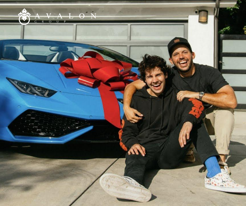 And there is a blue luxury sports car in the driveway.  A gay couple is posing in front of their new car.  Additionally there is a red bow on the car.