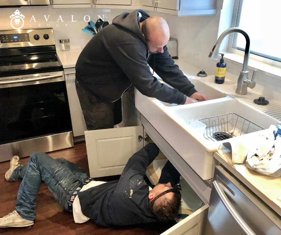 Additionally, two plumbers are working on a kitchen sink that is white. And one is under the sink and one is above. Also, the plumbers are wearing navy hoodies and blue jeans.
