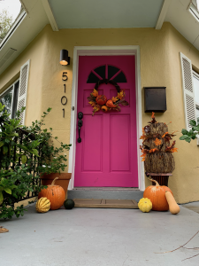 Hot pink front door of a yellow house with white trim. There are pumpkins bu the door and a thanksgiving wreath on the front door.