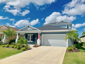 New 2 story home in Sarasota FL. The house is gray with white trim. There is a two car garage, a front porch with a USA flag mounted on a column. The house is flanked with beautiful landscaping.