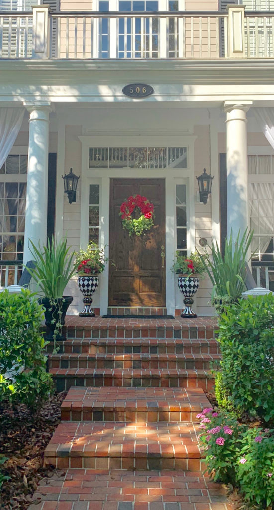 A home in Celebration Florida. There is a brick walkway lined with landscaping, potted flowers on both dives of front door. The house is yellow with white trim and a brown front door.