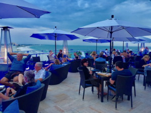The Level 11 Lounge on top of the Grand Plaza Hotel at St Pete Beach FL. There are tables with blue umbrellas, also sofas with blue cushions and the lounge is filled with patrons. In the background you see the Gulf of Mexico and St Pete Beach