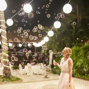 A backyard party with bubbles at night. There are patio string lights overhead.