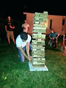 A young man playing giant jingo carefully removes a piece of wood from the bottom of the stack as other people look on.