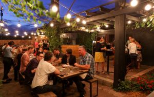 A backyard outdoor bar area is filled with people fellowshipping under patio string lights.