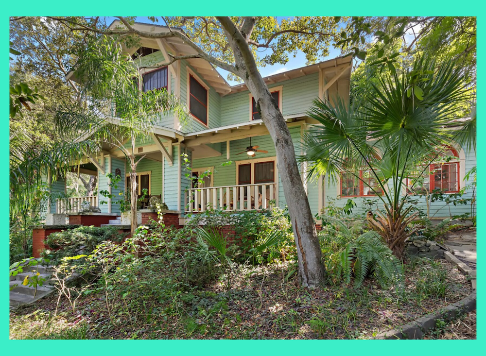 Craftsman home built in 1900 with green siding, cream trim color, in a wooded setting.