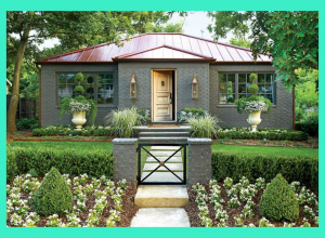 Gray brick home with metal burgundy roof. The landscaping utilizes annuals, shrubs and ground covers.