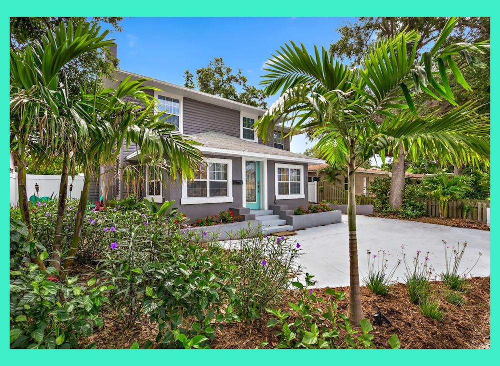 A great home built in 1925 with white trim and a teal front door. Grass has been removed and replaced with palm trees, shrubs and plants.