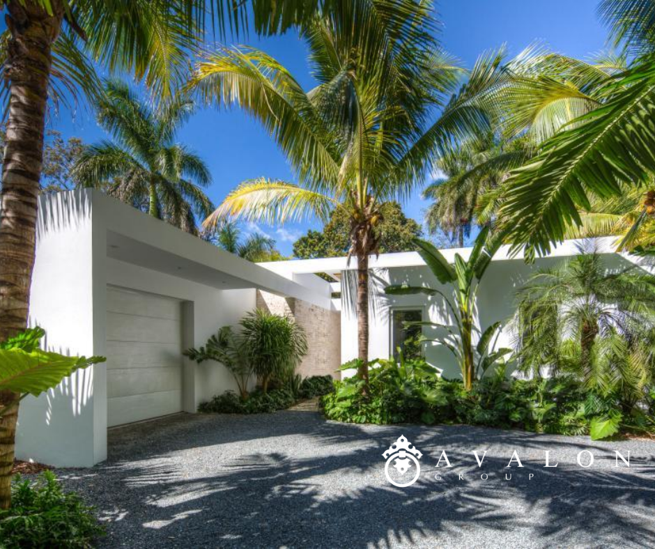 Furthermore, this mid century modern home 's exterior is white stucco.  And the palm trees with extra green fronds create a tropical paradise feeling.