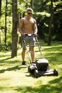 A man is cutting grass wearing gray shorts.