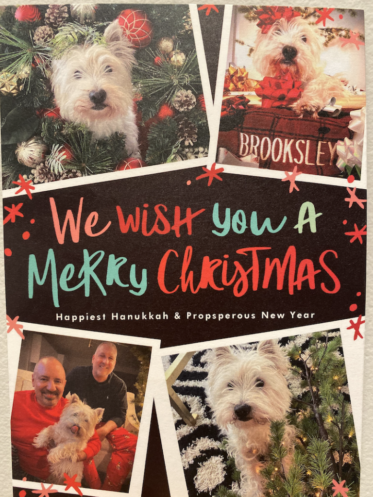 "Christmas Card says ""We wish you a merry Christmas, Happy Hanukkah, and a Prosperous New Year.  There are pictures of Brooksley the white West Highland Terrier and Rob and Aaron dressed in their Christmas pajamas."