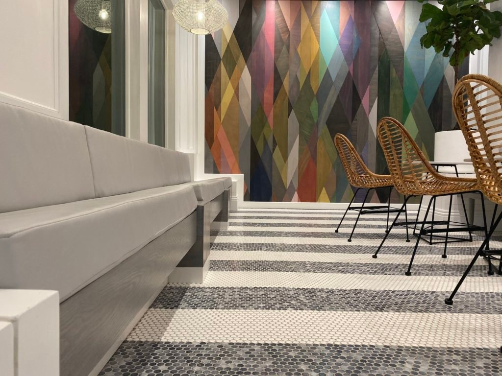 Gray bench, brown chairs with black legs, gray and white striped tile floor, Artistic wood stained wall in the colors of the rainbow.
