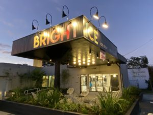 "This is a picture of the ""BRIGHT ICE"" ice cream, coffee, and pastry shop. There is a brown roof with bold letters saying ""Bright Ice."" There are planters surrounding the covered seating areas."