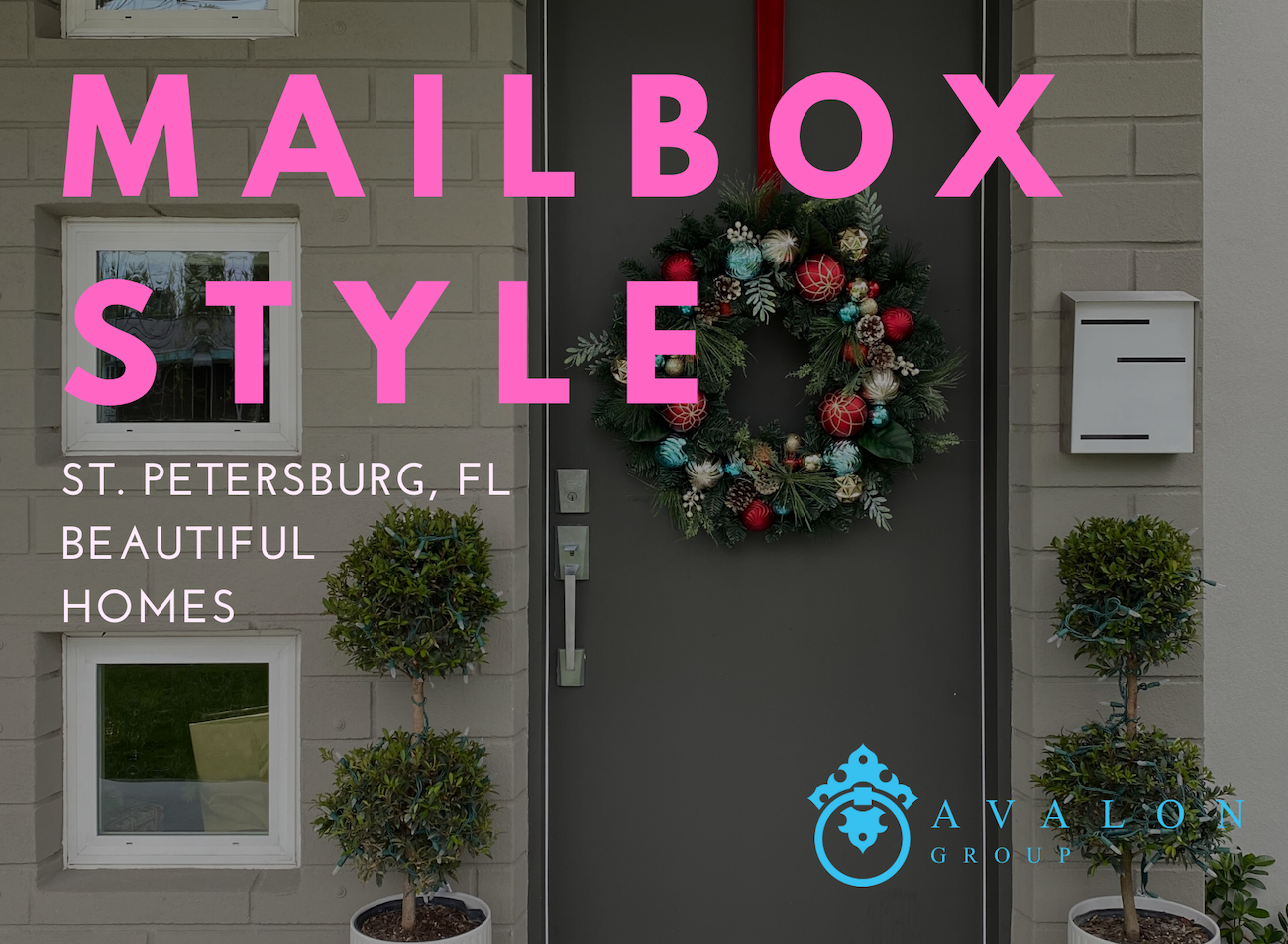 "Cover Picture for article ""Mailbox Style, St. Petersburg, Fl Beautiful Homes."" There is a house in the background. A close up of the front door that is dark gray flanked by two green topiaries. White trim around 3 windows, a wreath on the door with blue, red and silver balls, and a white mid-century modern mailbox."