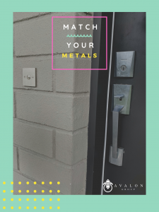 "Text of pictures states ""match your metals"". There is a gray door with a stainless steel door handle and stainless steel doorbell. There is a cement brick wall to the left. The border is sea foam green."