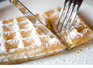 Golden square waffle with white powdered sugar on top. The is a knife and fork cutting into it.