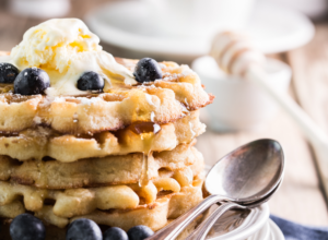 5 waffles stacked with scoop of butter on top, plus blueberries and maple syrup. The waffles are sitting on a white plate with two spoons.