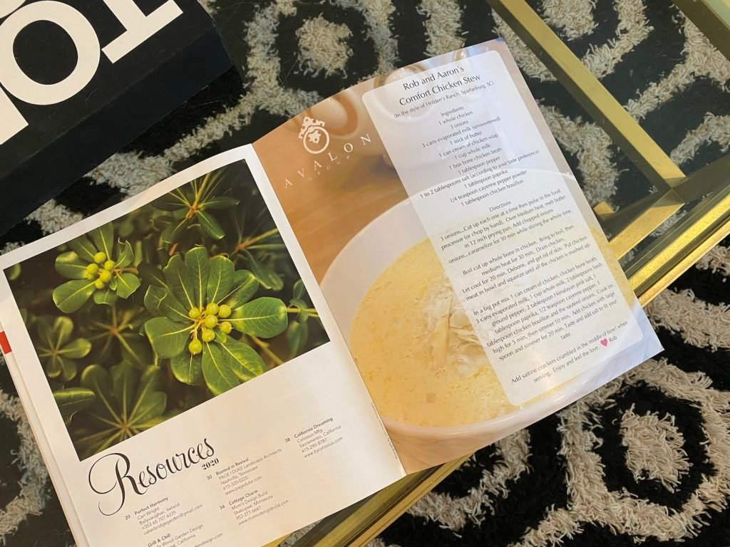 Home By Design Magazine by Avalon Group features our Chicken Stew Recipe on the inside back cover.  The magazine is on a glass coffee table with a black and white geometric rug underneath.
