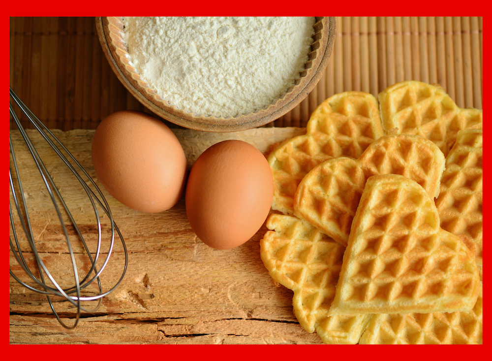 A whisk, two eggs, bowl of flour, and 7 heart shaped waffles stacked on top of a wooden table.
