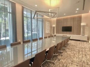 Large conference room of the ONE Condo Residences in St Petersburg, there is a glossy brown table with 30 brown leather chairs around it.