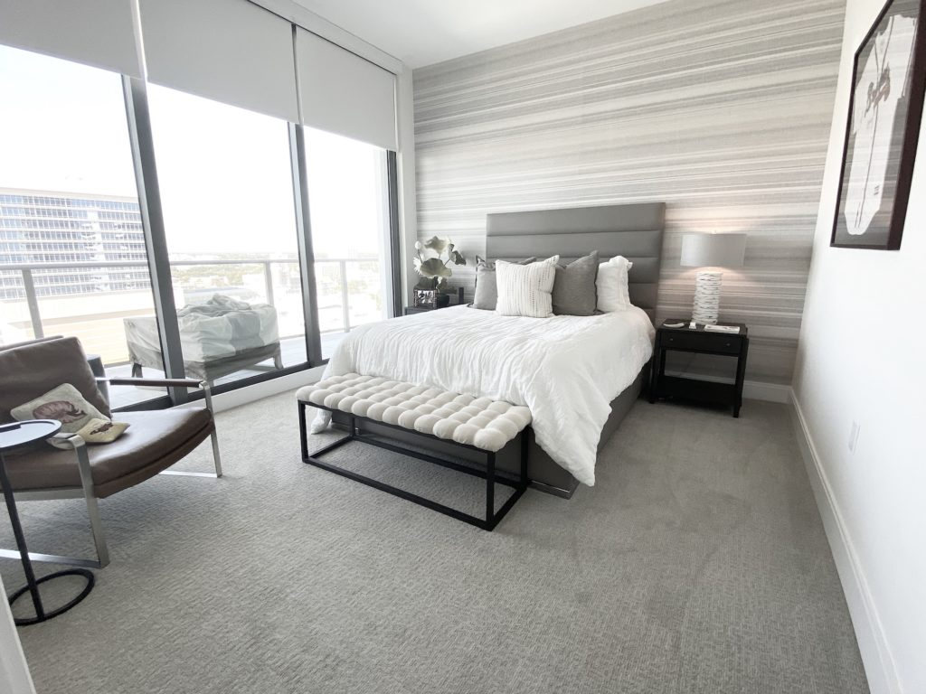 Glancing into the 2nd Bedroom Floor Plan A-05 of ONE St Petersburg FL Condos, you will see wall to ceiling sliding glass doors to balcony. As you continue into the room you will find gray floors, white bed and black nightstands.