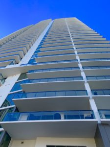 ONE Condos in St Petersburg FL with a view from the street looking up on the east side of the building. The building is white with glass and a blue sky above.