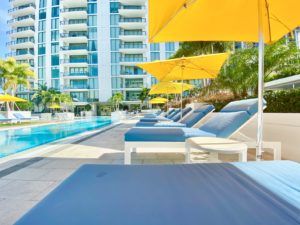 Blue lounge chairs and yellow umbrellas surround the pool at ONE Condos. The building is in the background.