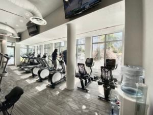 ONE Gym Exercise Bicycles are in front of windows overlooking the pool area