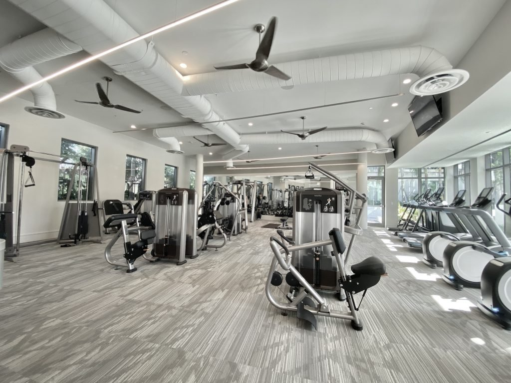 ONE St Petersburg FL Condos Neon white lights line the gym ceiling within the equipment lines gym with white walls and gray carpet.