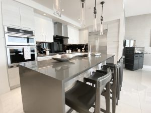"""One"" Condo Residences St Petersburg FL Kitchen in floor plan A-05 featuring a gray quartz countertop on the kitchen island. Th bar stools are black leather and drown wood legs."