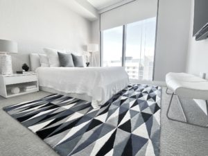 as you enter the 3rd Bedroom Floor Plan A-05 with black, you will see white and gray geometric triangle area rug, and a white bed. As you look to the far left you will see a sliding glass door to the balcony and a white chair with chrome legs.