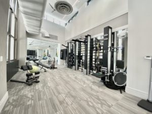 One gym has weight equipment lining the walls and a carpet floor that is beige with line designs.