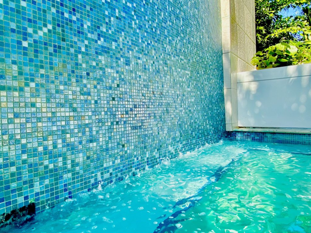 There is a blue iridescent tiled wall that has a waterfall flowing over it into the teal blue water at ONE St Petersburg FL Condos