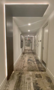 "Additionally the hallway carries the ONE design element inwall lights look like the top half of a Roman Numeral ""ONE"". The walls are beige, carpet is beige and gray."