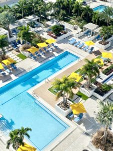 An L shaped pool that is aqua colored surrounded by brown walking areas, astro turf, palm trees and yellow umbrellas.
