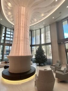 "The Lobby features a solitary column to carry out the ""one"" design elements. There is also a green Christmas tree to the right of the column."