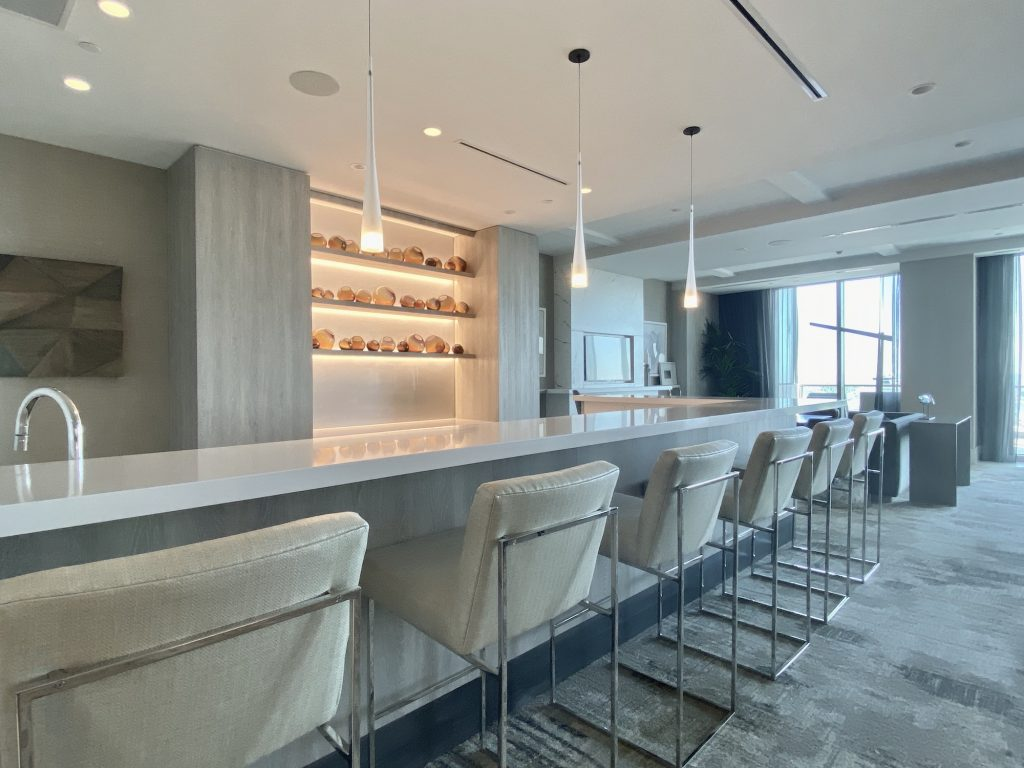 "The bar in ""Club One"" pictures has a white quartz countertop, beige bar chairs with chrome accents, lite shelves for spirits, and 3 modern light pendants."