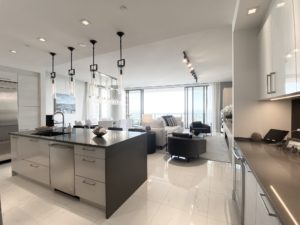 A kitchen island with black pendant lights above, a living area and dining room behind the island and in the background a balcony that overlooks tampa bay. ONE St Petersburg FL Condos