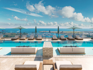 Also there is a pool on the 7th floor. In the picture the aqua colored pool is surrounded by a tan cement deck, white lounge chairs and a Bay view in the background.