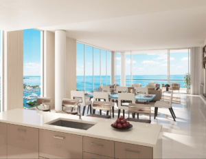 Furthermore, A wall of windows form a backdrop with views of Tampa Bay. The kitchen island features a gourmet sink, with living areas on the other side of it.