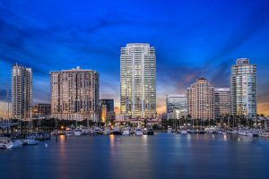 Picture of Downtown St Petersburg Fl from the water over Tampa Bay. The center of the pic shows the ONE St Petersburg FL Condos Building that is What with expanses of glass. Smaller high rises surround this building and the boat marina is featured at the base of the buildings.